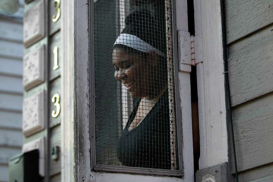 Resident Sheena Powell talks from her doorway in the Treme section of New Orleans. The historic New Orleans neighborhood where immigrants, free people of color and slaves were allowed to own property, worship on Sundays and gather in public to dance and play music, has hit a milestone. It was roughly 200 years ago that cottages were built and a community established just beyond the French Quarter in the area named for French milliner and property owner, Claude Treme. Photo: Gerald Herbert, Associated Press / AP