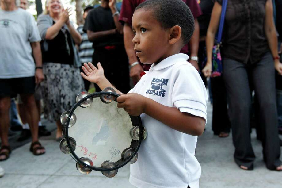 A young boy plays a tambourine at Armstrong Park in New Orleans. Photo: Gerald Herbert, Associated Press / AP