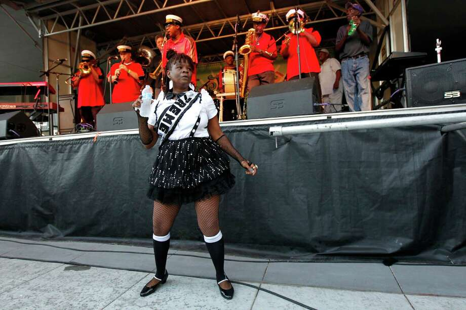 "Earlette Hodges, a Treme Baby Doll, performs with the Treme Brass band at an evening concert in Armstrong Park in the Treme section of New Orleans. The historic New Orleans neighborhood where immigrants, free people of color and slaves were allowed to own property, worship on Sundays and gather in public to dance and play music, has hit a milestone. It was roughly 200 years ago that cottages were built and a community established just beyond the French Quarter in the area named for French milliner and property owner, Claude Treme. The neighborhood is considered one of America's most unique, and it is getting a new lease on life thanks, in part, to the spotlight provided by HBO's series, ""Treme."" It's also at the center of a $4 billion redevelopment plan. (AP Photo/Gerald Herbert) Photo: Gerald Herbert, Associated Press / AP"