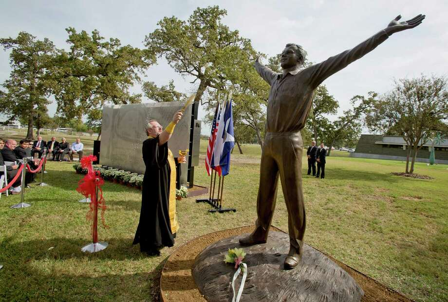 Father Lubomir Kupecz blesses the  statues of Yuri Gagarin and memorial to John Glenn with holy water at the city of Houston's parks department headquarters, which was the original NASA headquarters in Houston, Texas. Photo: Thomas B. Shea, For The Chronicle