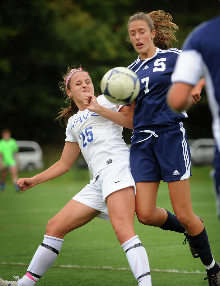 Darien's Dillon Schoen, left, battles for the ball with Staples' Meghan Lonergan during their soccer matchup at Darien High School on Monday, October 15, 2012. Photo: Brian A. Pounds / Connecticut Post