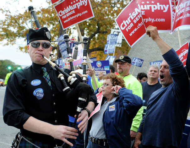 A bagpiper supporter of Republican Linda McMahon, left, walks past supporters for U.S. Rep. Chris Murphy, D-Conn.,  prior to a candidate's debate for an open U.S. Senate seat in New London, Conn., Monday, Oct. 15, 2012. (AP Photo/Jessica Hill) Photo: AP