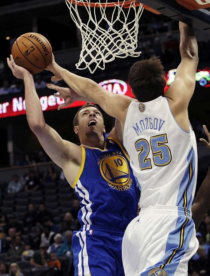 Warriors forward David Lee, who had 15 points, drives against Nuggets center Timofey Mozgov in a preseason loss in Denver. Photo: Joe Mahoney, Associated Press