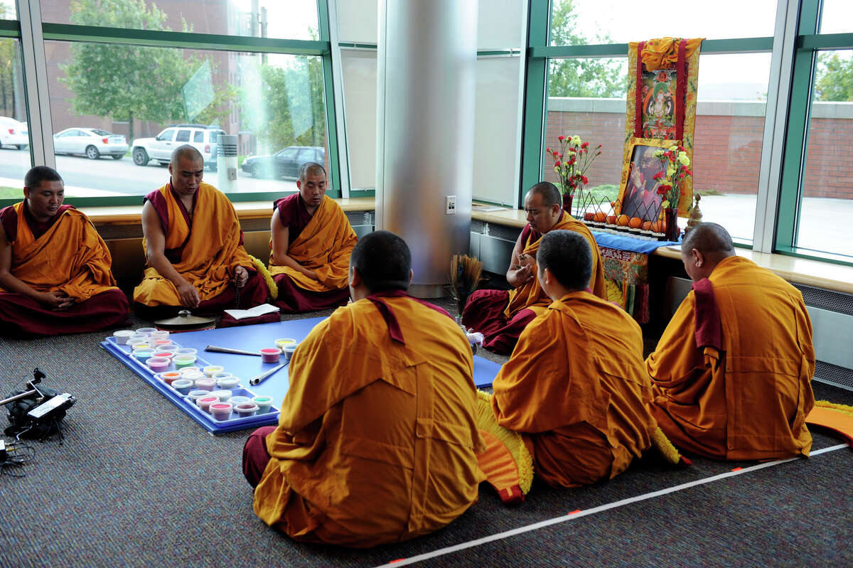 A group of Buddhist monks chant mantra prayers before beginning work on an intricate sand exhibit in the Student Center at the westside campus of Western Connecticut State University in Danbury Monday, Oct. 15, 2012.