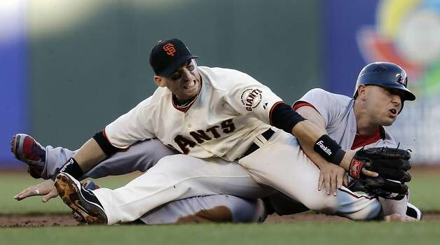 San Francisco Giants second baseman Marco Scutaro grimaces as his leg is caught under a sliding St. Louis Cardinals' Matt Holliday on a double play attempt during the first inning of Game 2 of baseball's National League championship series Monday, Oct. 15, 2012, in San Francisco. (AP Photo/Ben Margot) Photo: Ben Margot, Associated Press