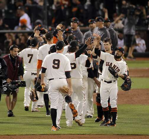 Sergio Romo high fives other players after the Giants defeated the Cardinals. The San Francisco Giants played the St. Louis Cardinals in Game 2 of the National League Championship Series on Monday, October 15, 2012, at AT&T Park in San Francisco, Calif. The Giants defeated the Cardinals 7-1. Photo: Carlos Avila Gonzalez, The Chronicle