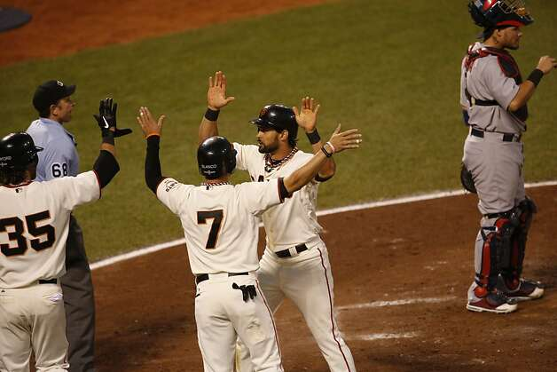 Brandon Crawford, left, and Gregor Blanco greet Angel Pagan at the plate in the 4th inning during game 2 of the NLCS on Monday, Oct. 15, 2012 at AT&T Park in San Francisco, Calif. Photo: Beck Diefenbach, Special To The Chronicle