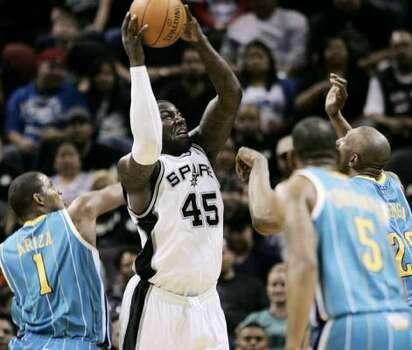 San Antonio Spurs' DeJuan Blair, middle left, shoots over New Orleans Hornets' Didier Ilunga-Mbenga, right, Marcus Thornton, middle right, and Trevor Ariza during the second half of an NBA basketball game, Saturday, Oct. 30, 2010, in San Antonio. New Orleans won 99-90. (AP Photo/Darren Abate) (Darren Abate / AP)