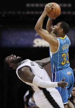 San Antonio Spurs' DeJuan Blair, left, is knocked down by New Orleans Hornets' Willie Green during the first half of an NBA basketball game, Sunday, Dec. 5, 2010. (Darren Abate/Special to the Express-News) (Darren Abate / Darren Abate/Special to the Expr)