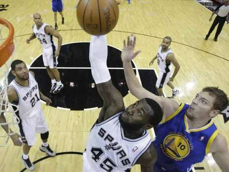 San Antonio Spurs' DeJuan Blair (45) pulls down a rebound in front of Golden State Warriors' David Lee (10) during the first quarter of an NBA basketball game, Wednesday, Dec. 8, 2010, in San Antonio. Spurs' Tim Duncan (21), Richard Jefferson (24), and Tony Parker (9) look on.  (AP Photo/Eric Gay) (Eric Gay / AP)