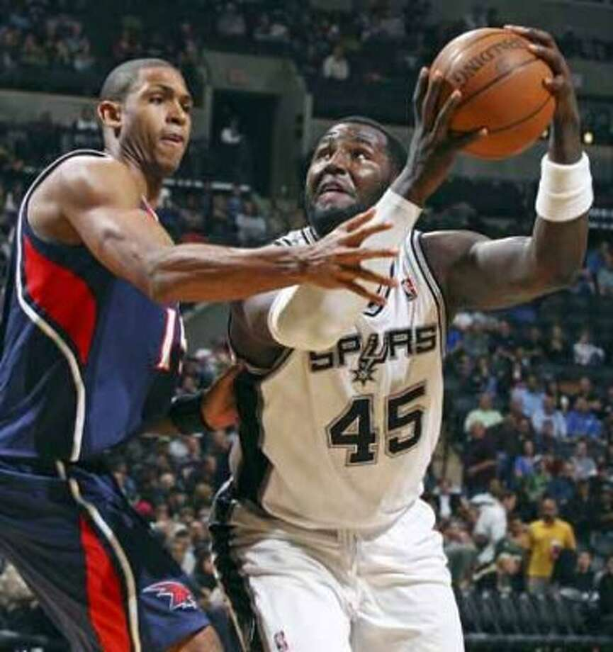 FOR SPORTS - Spurs' DeJuan Blair looks for room around Hawks' Al Horford during second half action Friday Dec. 10, 2010 at the AT&T Center. The Spurs won 108-92. (PHOTO BY EDWARD A. ORNELAS/eaornelas@express-news.net) (EDWARD A. ORNELAS / SAN ANTONIO EXPRESS-NEWS)