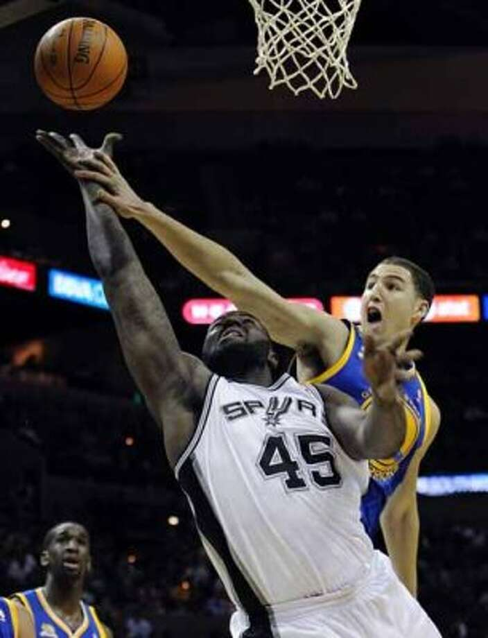 Spurs' DeJuan Blair (45) scores on a foul against the Golden State Warriors' Klay Thompson (11) in the first half at the AT&T Center on Wednesday, Jan. 4, 2012. Kin Man Hui/kmhui@express-news.net (SAN ANTONIO EXPRESS-NEWS)