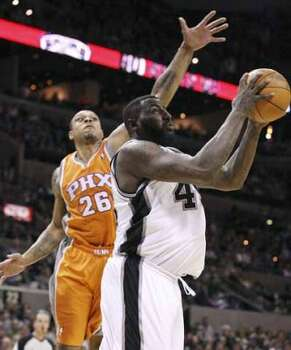 FOR SPORTS - San Antonio Spurs' DeJuan Blair shoots under Phoenix Suns' Shannon Brown during second half action Sunday Jan. 15, 2012 at the AT&T Center. The Spurs won 102-91. (PHOTO BY EDWARD A. ORNELAS/eaornelas@express-news.net) (SAN ANTONIO EXPRESS-NEWS)