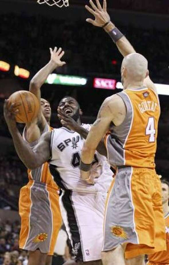FOR SPORTS - San Antonio Spurs' DeJuan Blair looks for room between Phoenix Suns' Channing Frye  and  Phoenix Suns' Marcin Gortat during second half action Sunday Jan. 15, 2012 at the AT&T Center. The Spurs won 102-91. (PHOTO BY EDWARD A. ORNELAS/eaornelas@express-news.net) (SAN ANTONIO EXPRESS-NEWS)