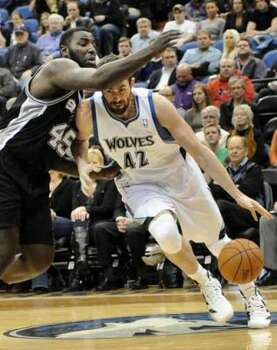 Minnesota Timberwolves' Kevin Love (42) drives around San Antonio Spurs' DeJuan Blair in the first half of an NBA basketball game, Friday, Jan. 27, 2012, in Minneapolis. (AP Photo/Jim Mone) (AP)