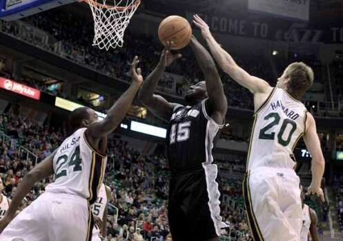 San Antonio Spurs forward DeJuan Blair (45) takes a shot while defended by Utah Jazz forward Paul Millsap (24) and guard Gordon Hayward (20) during the first half on an NBA basketball game, Monday, Feb. 20, 2012, in Salt Lake City. (AP Photo/Jim Urquhart) (AP)