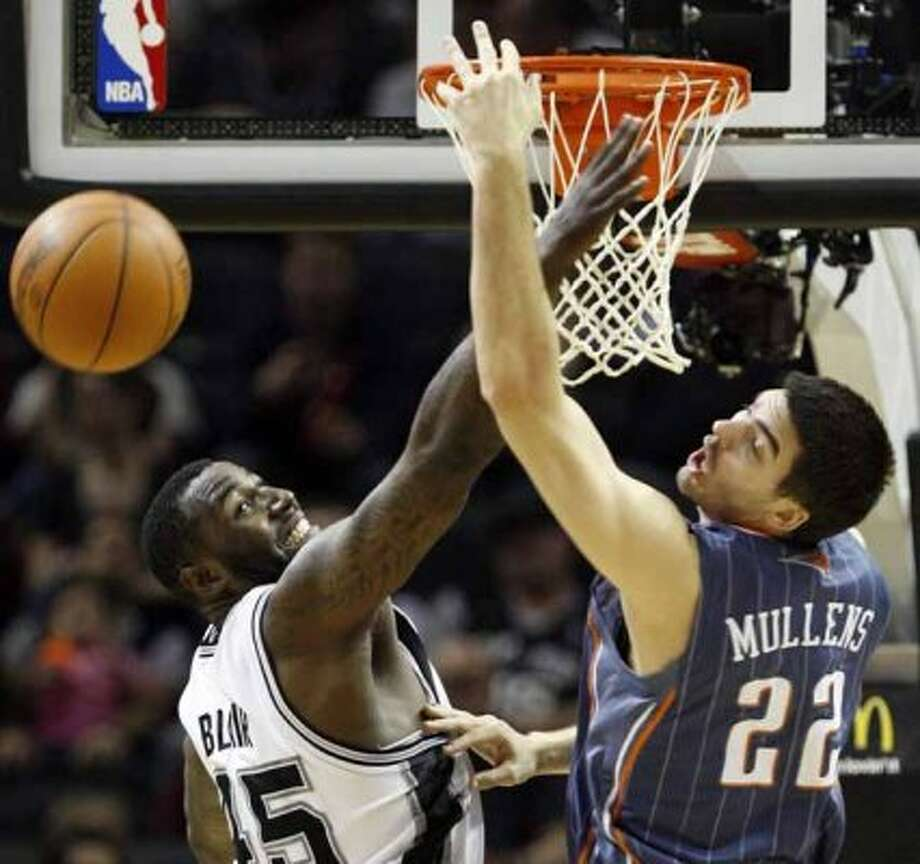 FOR SPORTS - San Antonio's DeJuan Blair, left, and Charlotte's Byron Mullens fight for a rebound during game action at the AT&T Center on Friday, March 2, 2012. San Antonio won 102-72. MICHAEL MILLER / mmiller@express-news.net (San Antonio Express-News)