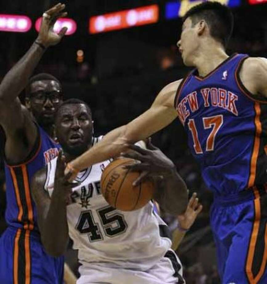 SPURS -- San Antonio Spurs DeJuan Blair grabs the rebound away from New York Knicks Amar'e Stoudemire, left, and Jeremy Lin during the second half at the AT&T Center, Wednesday, March 7, 2012. The Spurs won 118-105. Jerry Lara/San Antonio Express-News (San Antonio Express-News)