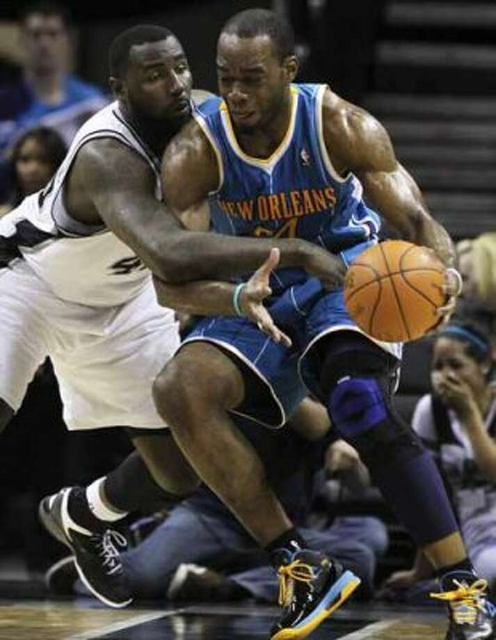 SPORTS   DeJuan Blair reaches in trying to foil Carl Landry on the blocks as the San Antonio Spurs play the New Orleans Hornets at the AT&T Center on April 6, 2012.  Tom Reel/ San Antonio Express-News (San Antonio Express-News)