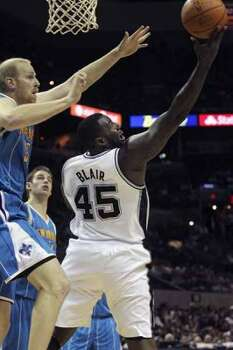 SPORTS   DeJuan Blair scores from the backdoor on Chris Kaman as the San Antonio Spurs play the New Orleans Hornets at the AT&T Center on April 6, 2012.  Tom Reel/ San Antonio Express-News (San Antonio Express-News)