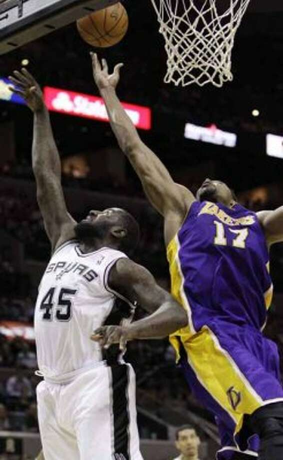 Los Angeles Lakers' Andrew Bynum (17) reaches over San Antonio Spurs' DeJuan Blair for a rebound during the first half of an NBA basketball game, Wednesday, April 11, 2012, in San Antonio. Bynum pulled down 30 rebounds. (AP Photo/Eric Gay) (AP)