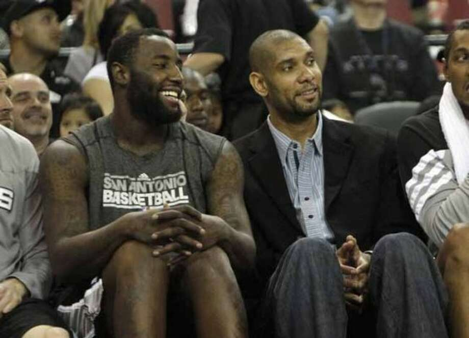 San Antonio Spurs' DeJuan Blair, left, and Tim Duncan smile while watching the closing minutes of their 127-102 win over the Sacramento Kings in a NBA basketball game in Sacramento, Calif., Wednesday, April 18, 2012.  Duncan did not suit up for the game.(AP Photo/Rich Pedroncelli) (AP)