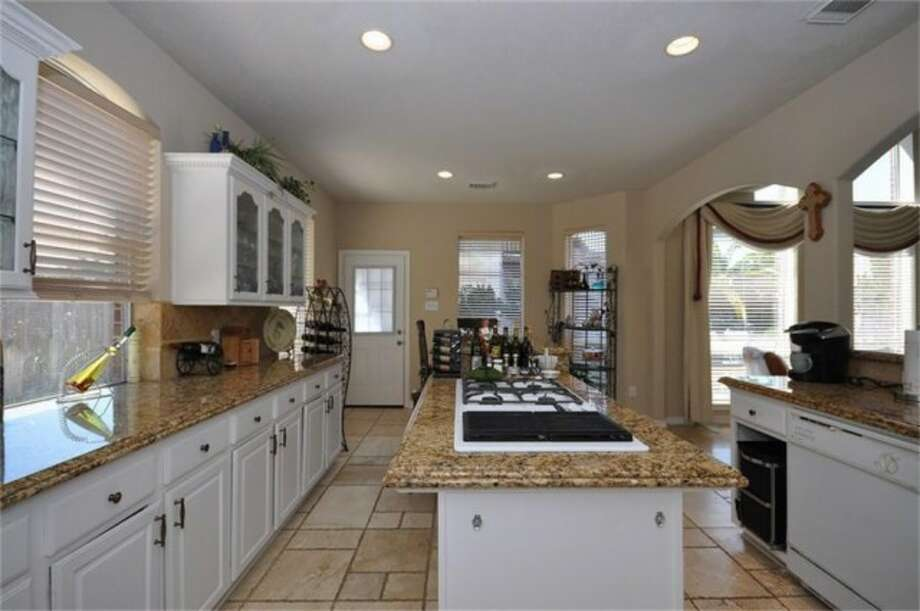 A gas range is located atop the island in the center of the room. Photo: Keller Williams