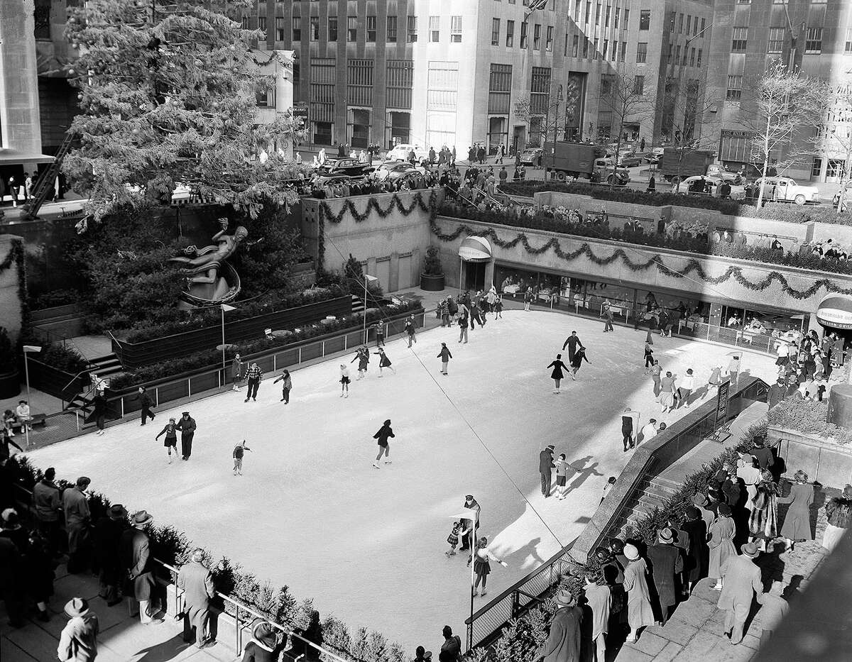 With the famed Rockefeller Center Christmas tree rising above them, skaters glide on the ice at the center's skating rink in midtown Manhattan in 1949.