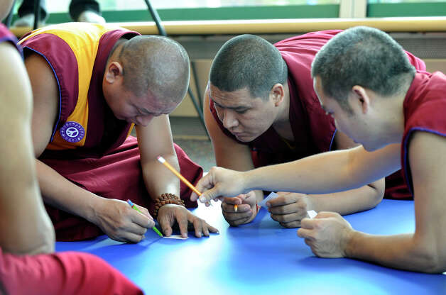 A group of Buddhist monks begin work on an intricate sand exhibit in the Student Center at the westside campus of Western Connecticut State University in Danbury Monday, Oct. 15, 2012. Photo: Carol Kaliff