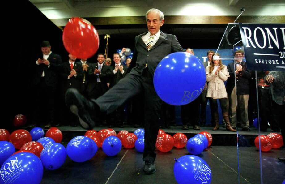 Ron Paul kicks balloons from the stage after speaking to supporters following his loss in the Maine