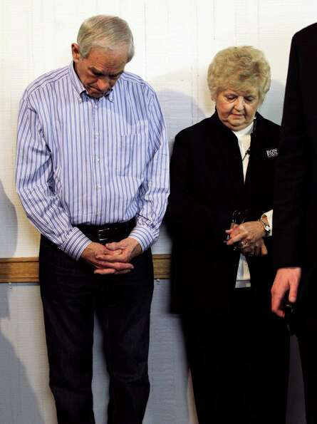 Ron Paul and his wife Carol bow their heads during a prayer to begin a Washington state Republican c
