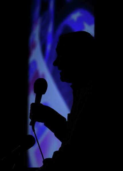 Ron Paul is silhouetted against a video backdrop as he speaks to voters taking part in Washington st