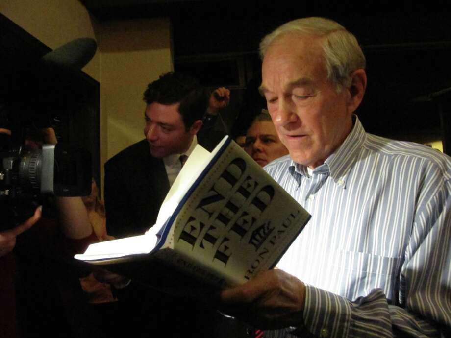 Ron Paul autographs his book for a fan during a campaign appearance Friday, Feb. 17, 2012 in Richland, Wash. Photo: Shannon Dininny, Associated Press / AP