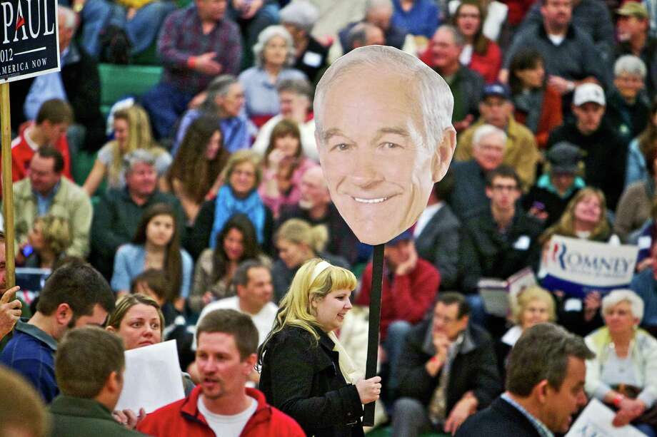 Christina Villagomez attracts the attention of caucus voters as she walks through the Lakeland High School gymnasium in Rathdrum, Idaho with an overside Ron Paul head Tuesday, March 6, 2012. (AP Photo/Coeur d'Alene Press, Jerome A. Pollos) MANDATORY CREDIT Photo: Jerome A Pollos, Associated Press / Coeur d'Alene Press