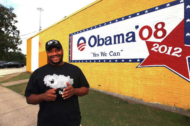 Marcus Davis, owner of The Breakfast Klub, shows the vandalized mural of President Barack Obama. Photo: .