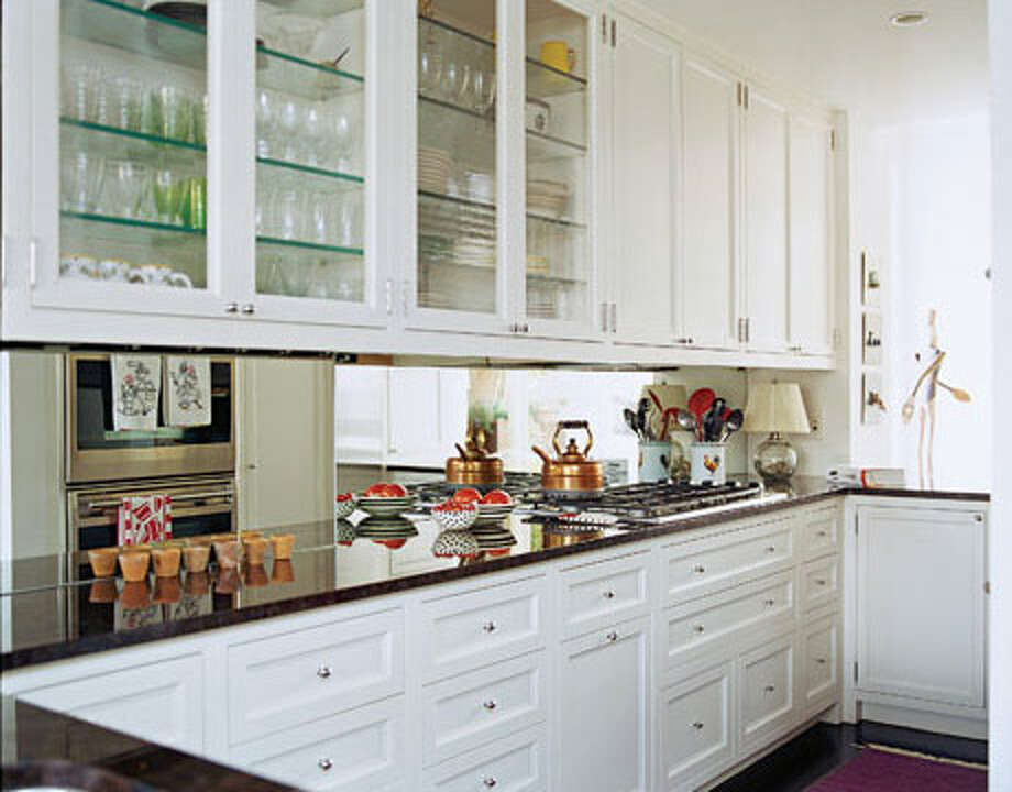 "Mirrors Work Magic A mirrored backsplash in this shabby-chic Manhattan apartment gives the illusion of more space. ""The kitchen opens up to the living room on one side and the family room, where we eat and watch TV, on the other,"" says designer Faye Cone. ""The idea was that it should be an extension of both these spaces.""  Reprinted with Permission of Hearst Communications, Inc. Originally Published: Space-Saving Tricks for Small Kitchens"