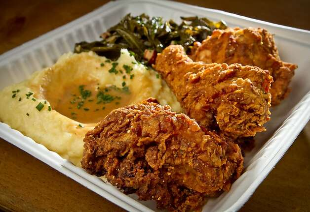 The fried chicken from the Front Porch across 29th Street is available at Rock Bar, where bartender Brion Nuda Rosch, right, phones in an order for a patron. Photo: John Storey, Special To The Chronicle