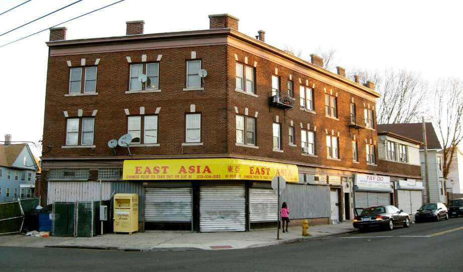 Nearly 20 people mostly Vietnamese, were evacuated from this apartment building at 50 Wood Avenue on Bridgeport's West End early Friday morning. A malfunctioning furnace flooded the building with dangerous carbon monoxide fumes. The residents were transported to a temporary shelter set up in the James J. Curiale School three blocks away. Photo: John Burgeson / Connecticut Post