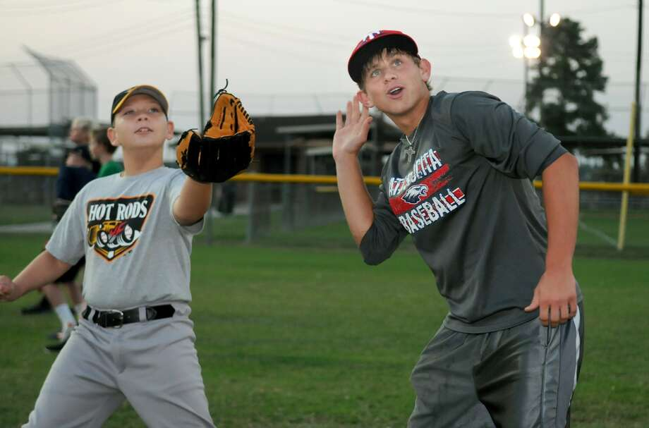 Atascocita High School junior and Eagles baseball player Hunter Stephenson, 17, right, warms up with Joshua Abernathy, 10, during game day for special needs kids at Lyndsey Lyons Sports Complex in Humble. Photo: Jerry Baker
