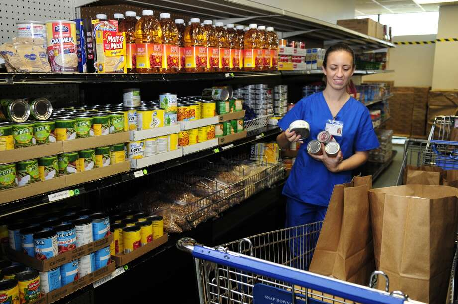 Kelsey Cockrell, 24, of Spring, who is a nursing student at Lone Star College - Montgomery, helps sort food donations at the Northwest Assistance Ministries Food Pantry. Photo: Jerry Baker / Greg Krenek