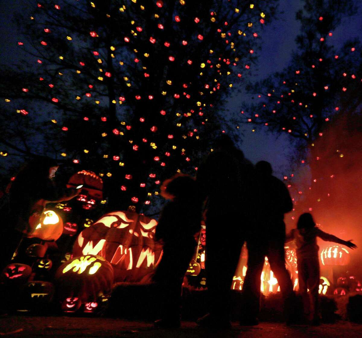 While surrounded by hundreds of pumpkins, a a group stops to look at the illuminated jack o' lanterns at the Roger Williams Park Zoo in Providence, R.I., Monday, Oct. 8, 2012. Some 5,000 carved pumpkins are on display for this year?'s Jack-o?'-lantern Spectacular, one of the nation?'s largest jack-o?'-lantern shows. (AP Photo/Charles Krupa)