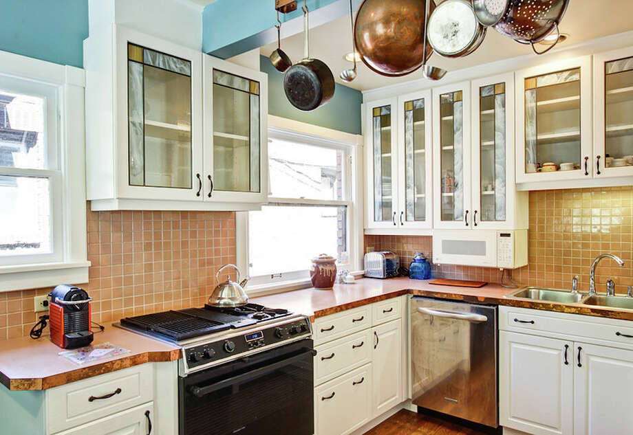 Kitchen of 1911 26th Ave. E. The 2,800-square-foot brick house, built in 1929, has three bedrooms, 1.5 bathrooms, Mahogany millwork and doors, a media/game room, a basement office, a patio and a garden on a 3,880-square-foot lot. It's listed for $675,000. Photo: Val Mohney, Courtesy Donovan Shelton And Scott Burdette/Windermere Real Estate