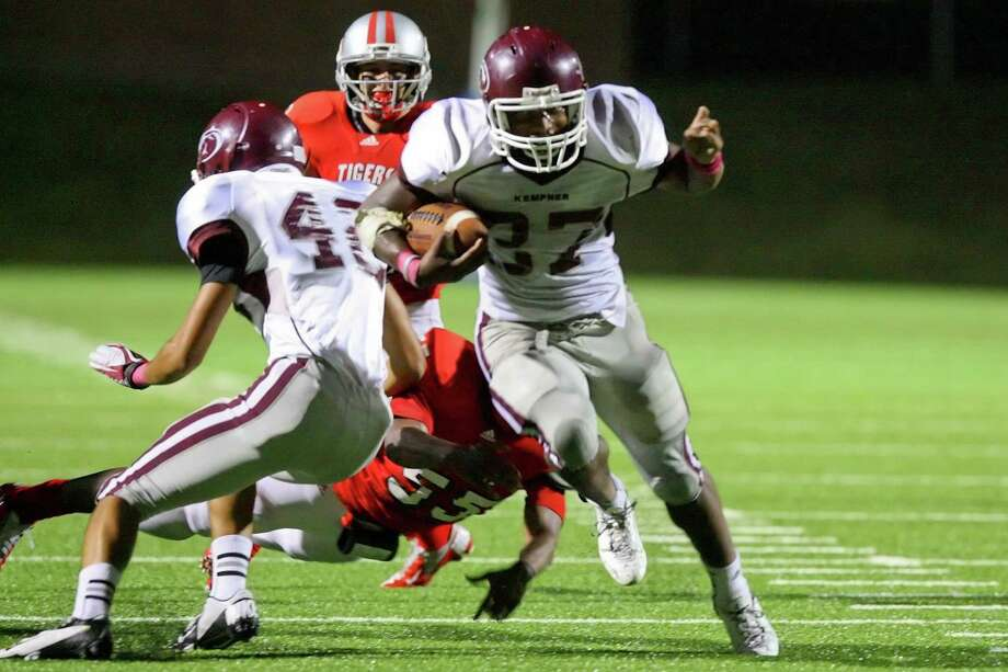 Kempner fullback Armond Weh-Weh cuts up the middle and past the Travis defenders as he makes a first down run Saturday night. Photo: Matthew White / Freelance