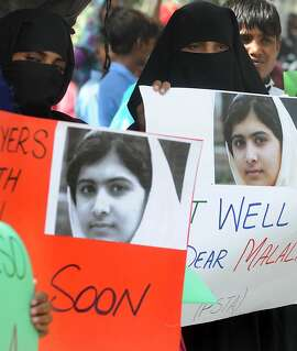 Pakistani students carry placards with the photographs of child activist Malala Yousafzai during a protest against the assassination attempt by the Taliban on Malala in Lahore on October 16, 2012. In an attack which outraged the world, Malala was shot on a school bus in the former Taliban stronghold of the Swat valley last Tuesday as a punishment for campaigning for the right to an education. AFP PHOTO / ARIF ALIArif Ali/AFP/Getty Images