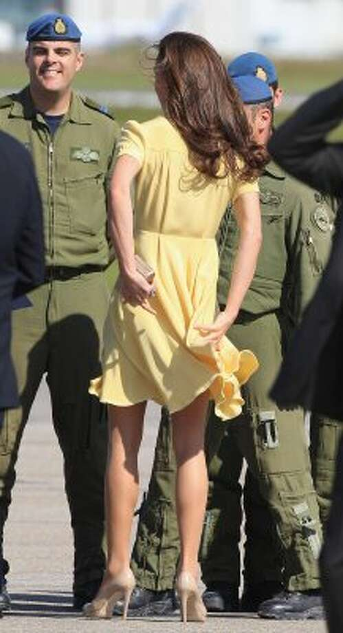 Catherine, Duchess of Cambridge, holds her dress down while speaking to soldiers at the Calgary Airport last July.  (Chris Jackson / Getty Images)