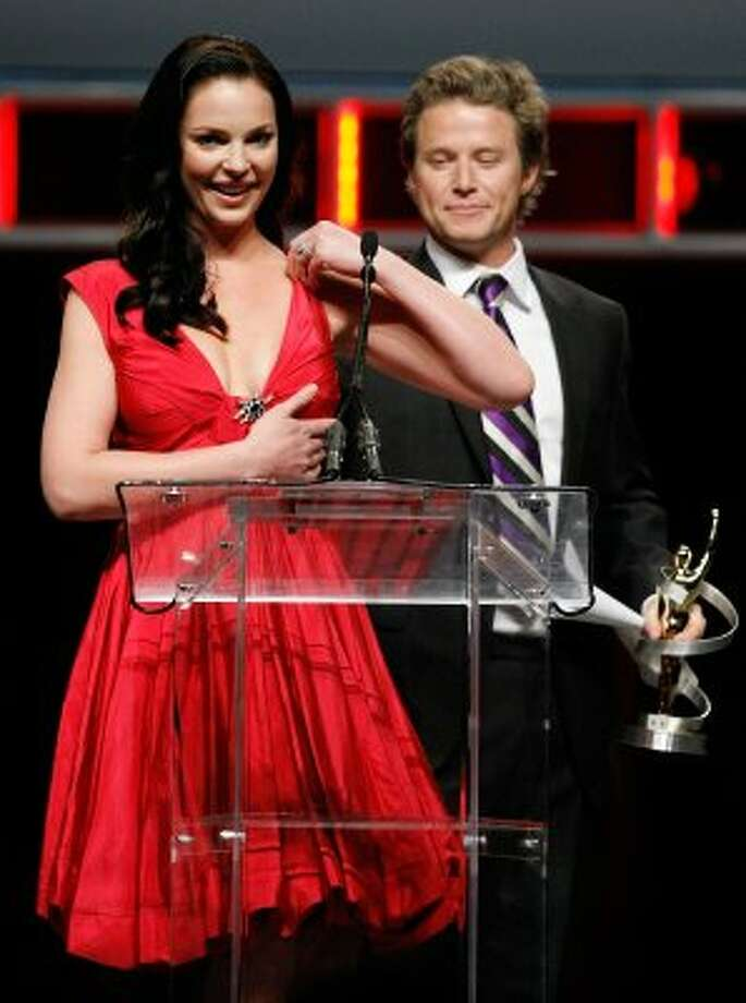 Showest awards host Billy Bush holds up Katherine Heigl's dress after it broke while she was accepting an acting award.  (Ethan Miller / Getty Images)