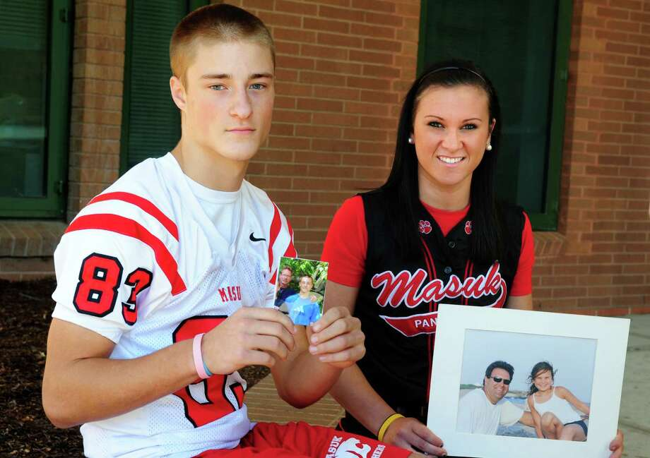 Masuk High School juniors, Russell Lilly, a football player, and Tatum Buckley, a softball player, hold photos of their fathers.  The students both recently lost their fathers and have found an outlet in athletics and support from their teammates during this time. Photo: Autumn Driscoll / Connecticut Post