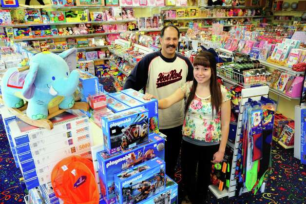 Owner Lou Mitri and his fifteen-year-old daughter, Rachel, stand among some of the educational toys at Joggen Your Noggin in Monroe.  The family-owned store is celebrating 15 years in business, Oct. 17, 2012. Photo: Autumn Driscoll / Connecticut Post