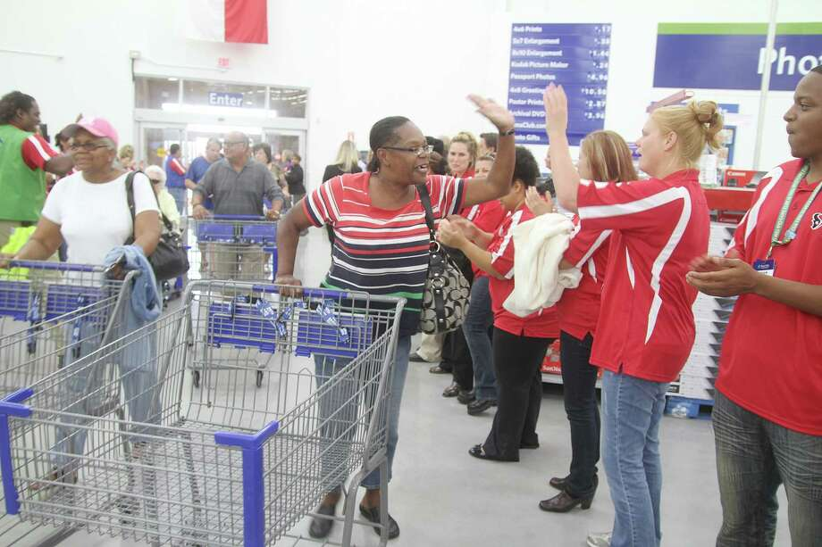Laura Joseph of Houston gives associates high fives during the grand opening of Sam's Club in Pearland. Photo: Pin Lim / Copyright Pin Lim.