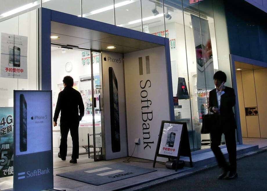 In this Oct. 12, 2012 file photo, a man walks in a shop of Japan's cellphone company Softbank Corp. in Tokyo. Softbank on Monday announced plans to buy a 70 percent stake in U.S. mobile phone carrier Sprint Nextel Corp. for $20 billion. (AP Photo) Photo: Shizuo Kambayashi, Associated Press / AP